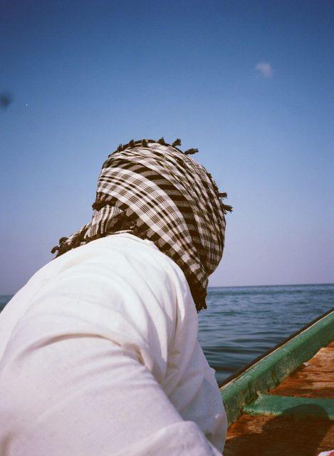 Oman x 衣 クーフィーヤと呼ばれる布をかぶった男性。乾燥した日差しの強いこの地域ならではです。頭を日差しから守り、砂嵐の時には鼻と口を覆うことができる便利なクーフィーヤは、白一色、白黒のチェック、赤白のチェックの3種類が主流ですが、現在若者の間ではファッションアイテムの一つとして様々な色のクーフィーヤが着用されるようになっています。