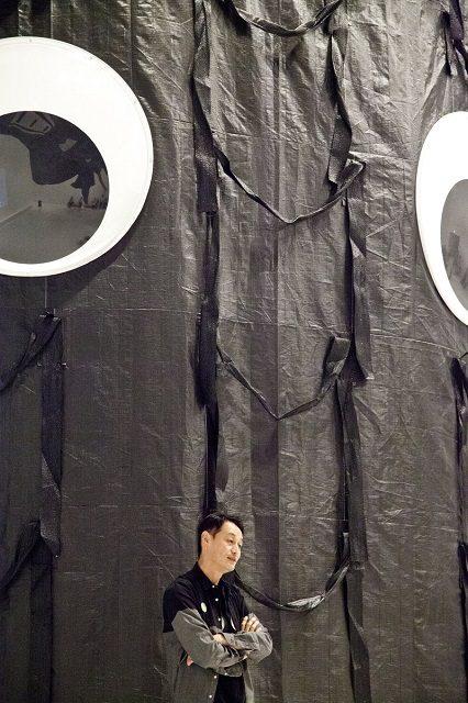 福島の汚染廃棄袋で作成した高さ6.9Mの彫刻《DADAモレ》2017 の前に立つ岡本光博さん