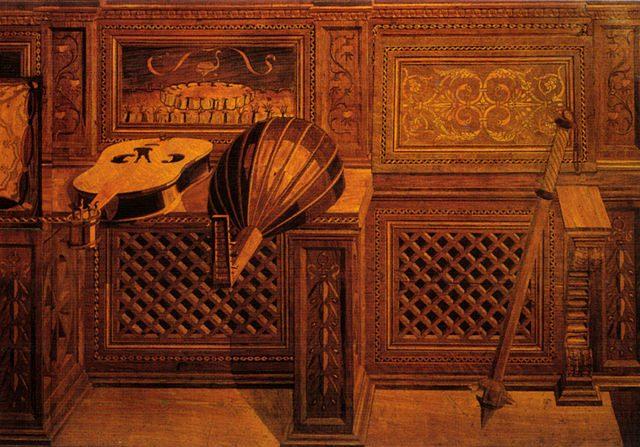 ウルビーノの宮殿内にあるフェデリーコ公爵の書斎の壁を飾るパネル。遠近法がこれでもかと駆使されて描かれた楽器。1473年頃。